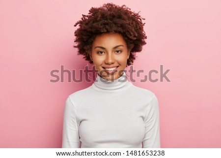 Gorgeous lovely curly woman with Afro hairstyle, feels glad, smiles gently at camera, wears optical  Stock photo © vkstudio