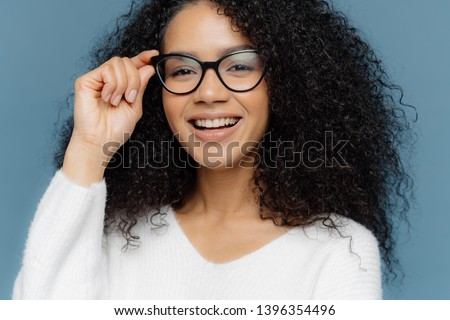 Cropped shot of good looking woman wears optical glasses, smiles broadly, shows white perfect teeth, Stock photo © vkstudio