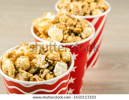 three red cardboard cup in a row with sugar popcorn on a wooden  Stock photo © mizar_21984