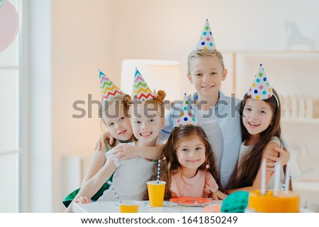 Group of adorable kids wear party hats, embrace and have fun, celebrate birthday, pose in decorated  Stock photo © vkstudio