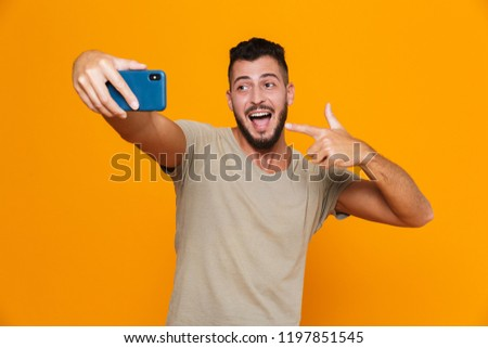 Happy attractive caucasian man in orange t-shirt, hold hands in jeans pockets, smiling upbeat, havin Stock photo © benzoix