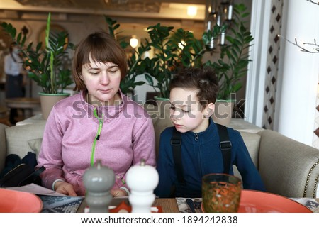 Mother with her son looking at menu in restaurant Stock photo © galitskaya