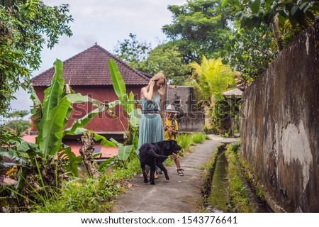 Bali dog. Mother and son tourists in Bali walks along the narrow cozy streets of Ubud. Bali is a pop Stock photo © galitskaya