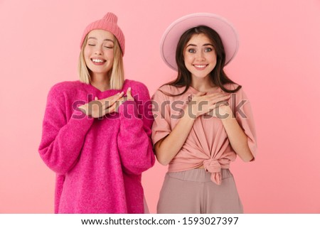 Image of two women in girlish clothes smiling and keeping finger Stock photo © deandrobot