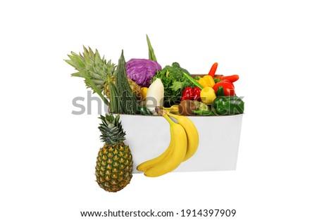 Grocery shopping bag with organic exotic fruits on white background. Stock photo © Illia