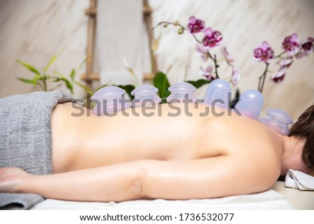 Cups applied to back skin of a female patient as part of the tra Stock photo © boggy