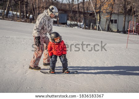 Dad teaches son snowboarding. Activities for children in winter. Children's winter sport. Lifestyle  Stock photo © galitskaya