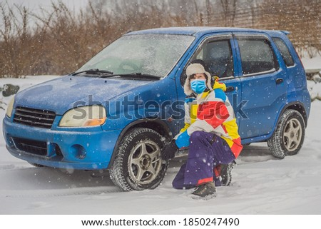 Winter accident on the road. A man changes a wheel during a snowfall. Winter problems Stock photo © galitskaya