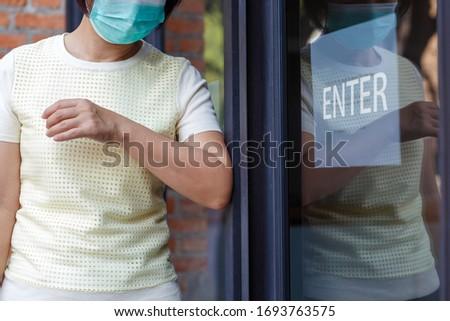 Mulher máscara abertura porta cotovelo Foto stock © galitskaya