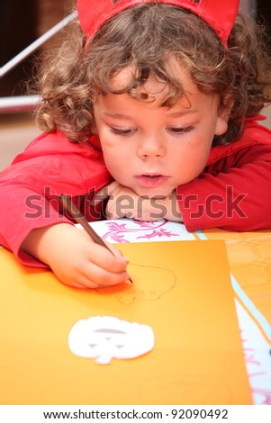 Closeup of a child in a red devil's outfit drawing jack-o-lanterns Stock photo © photography33