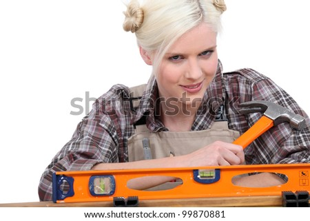 handywoman wearing a checked shirt and holding a hammer behind a level Stock photo © photography33
