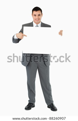 Businessman pointing at sign he is holding against a white background stock photo © wavebreak_media