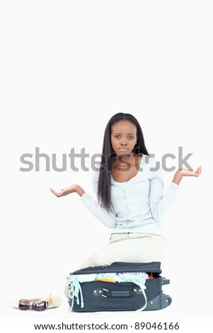 Young woman has no idea how to get her suitcase closed against a white background stock photo © wavebreak_media