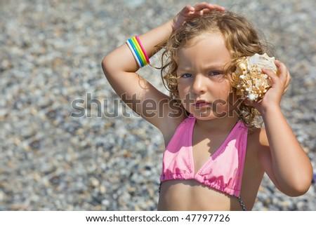 pretty little girl has leant seashell bowl to an ear on seacoast Stock photo © Paha_L