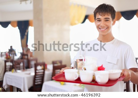Stock photo: young smiling affable waiter keeps tray with dishes at restauran