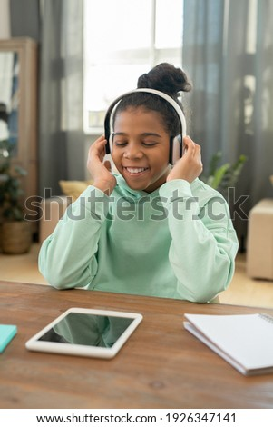 Smiling cute african young man with tablet listening to music Stock photo © deandrobot