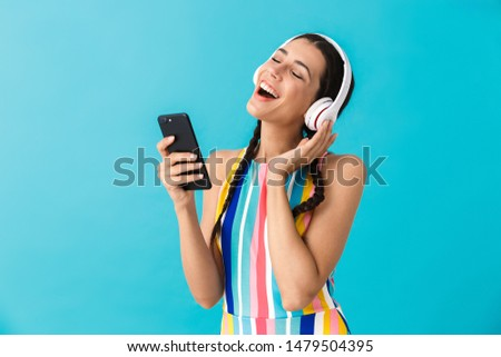 Smiling brunette woman in blue dress listening music with boombox Stock photo © deandrobot