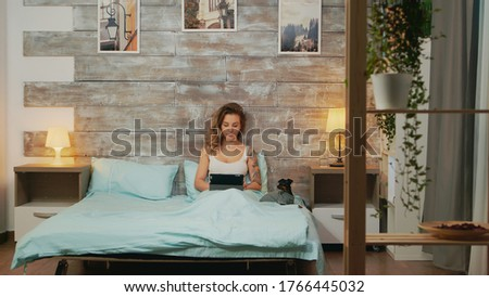 Stock photo: Young woman using her tablet computer in her bed late at night