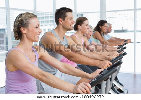 senior man and young woman spinning in fitness bike at the gym Stock photo © Kzenon