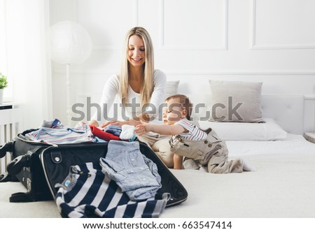 Stock photo: Travelling with kids. Happy mother with her child packing clothes for holiday