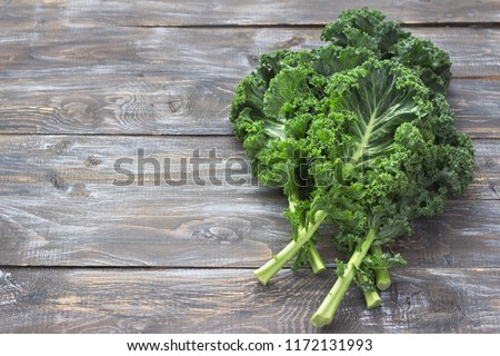 Fresh leaf of kale cabbage on wooden background. Green vegetable leaves. Top view . Healthy eating,  stock photo © Virgin
