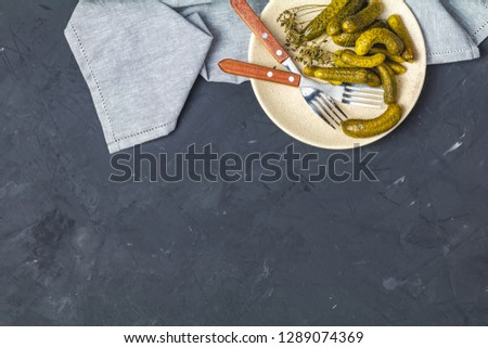 Pickled gherkins or cucumbers in plate on back concrete surface  Stock photo © artsvitlyna