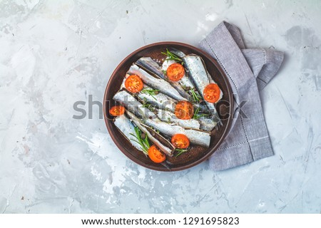 Stock photo: Raw uncooked sea fish with parsley on light gray concrete table