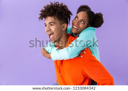 Photo of pleased african american man piggybacking his teenage s Stock photo © deandrobot