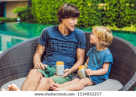 Father and son eat dessert with chia seeds and mangoes by the pool in the morning. healthy eating, v Stock fotó © galitskaya