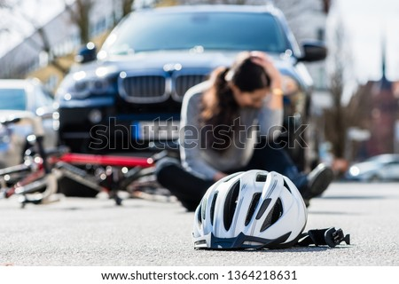 Helmet on the asphalt after accidental collision between bicycle and car Photo stock © Kzenon