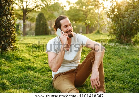 Picture of sociable young man in casual wear sitting on grass in Stock photo © deandrobot