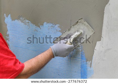 Wall insulation, spreading mortar over mesh and styrofoam, polys Stock photo © simazoran