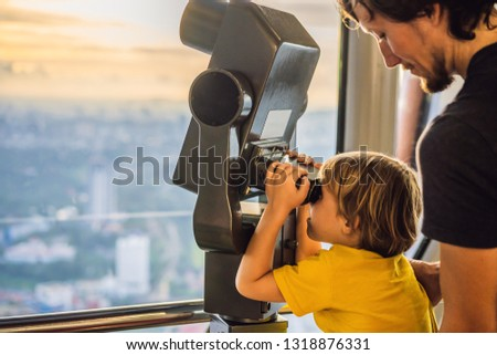 Dad and son are looking at Kuala lumpur cityscape. Use binoculars. Panoramic view of Kuala Lumpur ci Stock photo © galitskaya