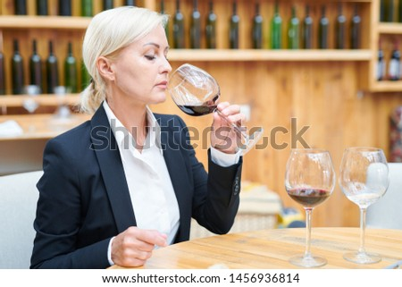 Elegant sommelier sitting by table in cellar and tasting cabernet from wineglass Stock photo © pressmaster