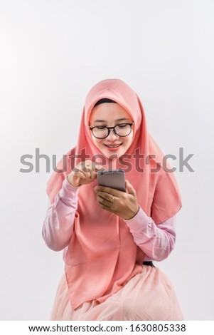 Pretty young muslim woman in hijab scrolling in smartphone outdoors Stock photo © pressmaster