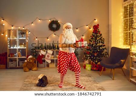 santa claus secretly putting gift boxes by the christmas tree stock photo © dashapetrenko