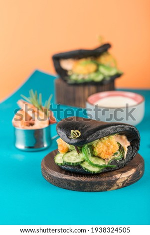 Healthy homemade burger with fresh shrimp and vegetables above the hand on a light background. Stock photo © artjazz