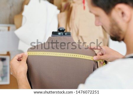 Male tailor measuring back of new jacket on dummy during work Stock photo © pressmaster