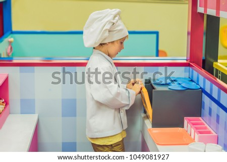 Boy plays the game as if he were a cook in a children's kitchen Stock photo © galitskaya