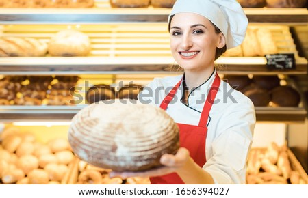 Saleswoman with apron presenting fresh bread in a bakery shop Stock photo © Kzenon