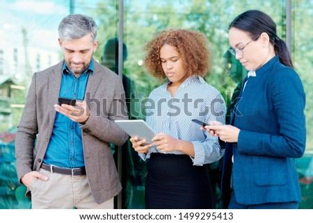 Row of young employees with mobile gadgets organizing work or surfing in the net Stock photo © pressmaster