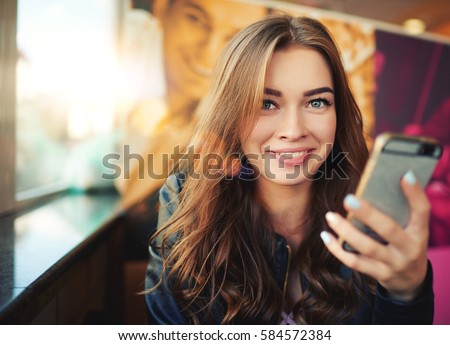 Cheerful girl watching funny video in smartphone while sitting in cafe Stock photo © pressmaster