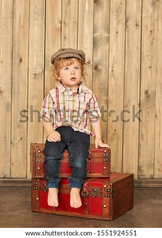 Old-fashioned little boy sitting at a vintage wooden carriage Stock photo © galitskaya