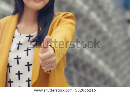 Pretty businesswoman holding thumb up in front of positive busin Stock photo © lichtmeister