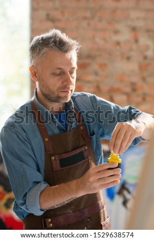 Mature painter in workwear uncovering plastic jar with gouache Stock photo © pressmaster
