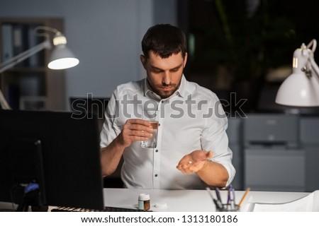 businessman taking medicine pill at night office Stock photo © dolgachov
