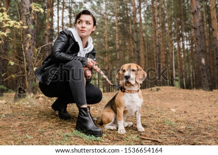 Brunette girl in casualwear sitting on squats during chill with beagle puppy Stock photo © pressmaster