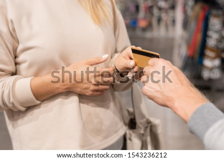 Hand of young man passing his wife credit card to pay for purchase Stock photo © pressmaster