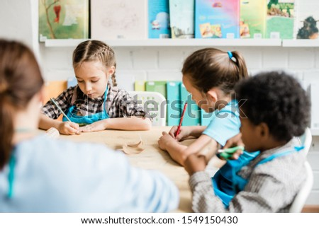 Group of diligent schoolkids sitting by table and making halloween decorations Stock photo © pressmaster