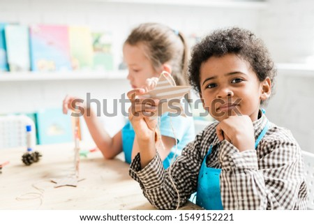 Diligent African youngster holding handmade Christmas star shaped decoration Stock photo © pressmaster